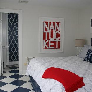 Modelo de habitación de invitados costera, de tamaño medio, sin chimenea, con paredes grises, suelo de baldosas de cerámica y suelo azul