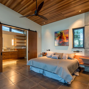Design ideas for a small modern loft-style bedroom in Seattle with yellow walls, porcelain floors, a two-sided fireplace, a stone fireplace surround and beige floor.