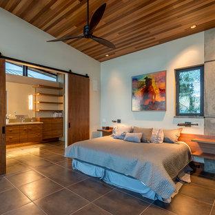 Diseño de dormitorio tipo loft, moderno, pequeño, con paredes amarillas, suelo de baldosas de porcelana, chimenea de doble cara, marco de chimenea de piedra y suelo beige