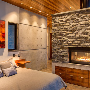 Пример оригинального дизайна: маленькая спальня на антресоли в стиле модернизм с белыми стенами, полом из керамогранита, печью-буржуйкой, фасадом камина из камня и бежевым полом