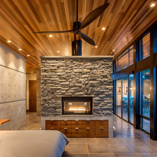 Inspiration for a small modern loft-style bedroom in Seattle with grey walls, porcelain floors, a two-sided fireplace, a tile fireplace surround and beige floor.