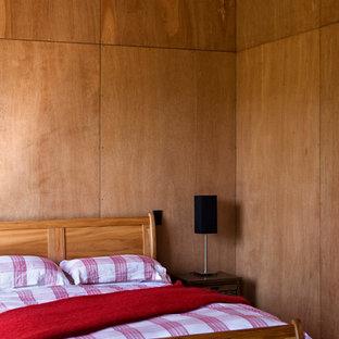 Bild på ett rustikt sovrum, med bruna väggar