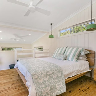 Beach style bedroom in Central Coast with white walls, medium hardwood floors and brown floor.