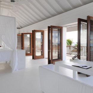 Aménagement d'une très grand chambre parentale exotique avec un mur blanc, béton au sol, aucune cheminée et un sol blanc.