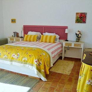 Modelo de dormitorio principal, marinero, grande, con paredes blancas y suelo de baldosas de terracota