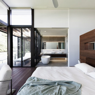 Design ideas for a large contemporary master bedroom in Central Coast with white walls, dark hardwood floors and brown floor.