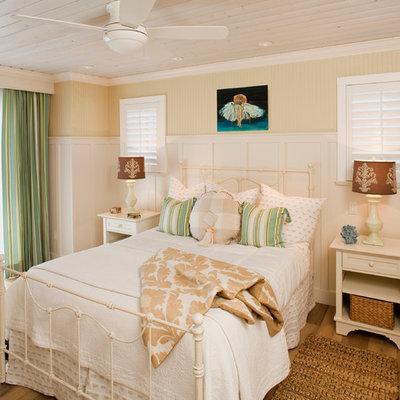 Beach style master medium tone wood floor bedroom photo in Los Angeles with beige walls