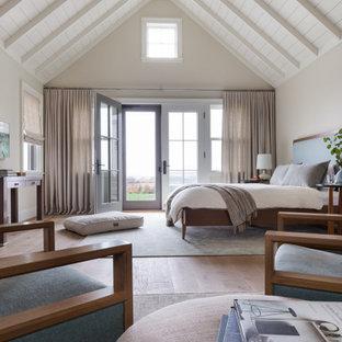 Modelo de dormitorio machihembrado y abovedado, marinero, con paredes beige, suelo de madera en tonos medios y suelo marrón