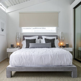 Inspiration for a small beach style guest light wood floor bedroom remodel in Los Angeles with white walls