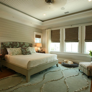 Photo of a mid-sized tropical master bedroom in Atlanta with beige walls, medium hardwood floors and no fireplace.