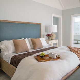 Example of a coastal master beige floor bedroom design in Boston with gray walls