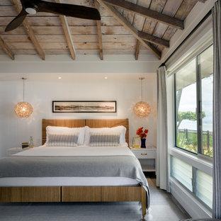 Cette image montre une chambre parentale marine de taille moyenne avec un mur blanc, un sol en carrelage de porcelaine, un sol gris, un plafond en poutres apparentes et du lambris de bois.