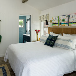 Photo of a mid-sized beach style guest bedroom in Hawaii with white walls, porcelain floors, grey floor, exposed beam and panelled walls.