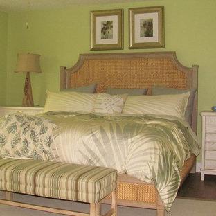 Ejemplo de dormitorio principal, costero, de tamaño medio, sin chimenea, con paredes verdes y suelo laminado
