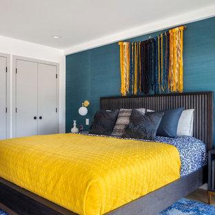 Imagen de habitación de invitados contemporánea, grande, sin chimenea, con paredes azules, suelo de madera clara y suelo beige