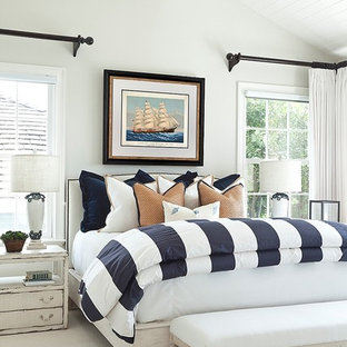 Example of a beach style master carpeted bedroom design in Orange County with white walls and no fireplace