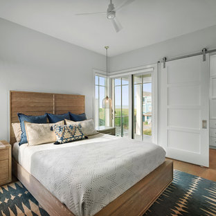Example of a large coastal master medium tone wood floor and brown floor bedroom design in Other with gray walls
