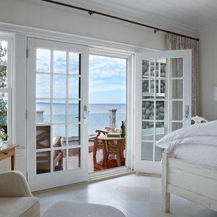 Foto på ett maritimt sovrum, med vita väggar, målat trägolv och flerfärgat golv