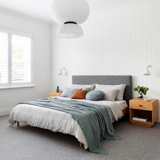 Mid-sized beach style master bedroom in Melbourne with white walls, carpet, a corner fireplace and grey floor.