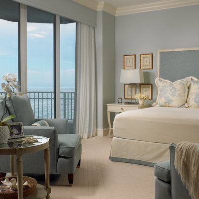 Example of a beach style carpeted bedroom design in Miami with blue walls