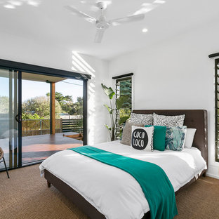 Inspiration for a beach style guest bedroom in Other with white walls, carpet and brown floor.