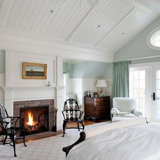 Diseño de dormitorio marinero con paredes azules, marco de chimenea de ladrillo y chimenea tradicional