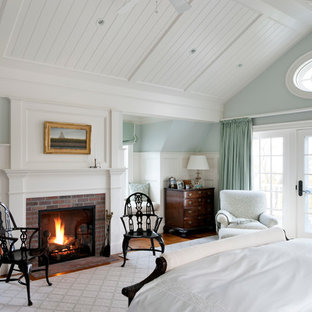 Beach style bedroom photo in Boston with blue walls, a brick fireplace and a standard fireplace