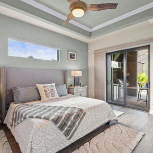 Inspiration for a coastal light wood floor and gray floor bedroom remodel in Miami with beige walls