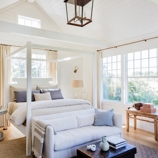 Example of a large coastal master light wood floor bedroom design in Other with white walls and no fireplace