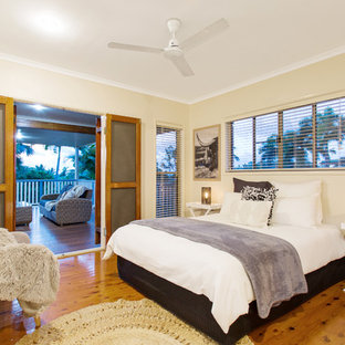 Design ideas for a beach style master bedroom in Brisbane with beige walls, medium hardwood floors and brown floor.