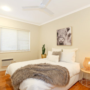 This is an example of a beach style guest bedroom in Brisbane with beige walls, medium hardwood floors and brown floor.