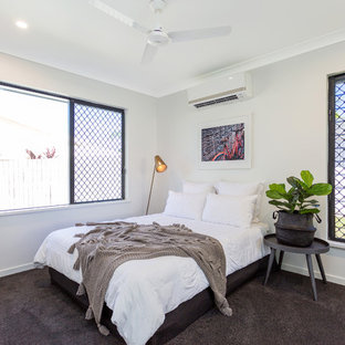 This is an example of a beach style guest bedroom in Other with grey walls, carpet and brown floor.