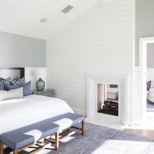 Modelo de dormitorio costero con paredes grises, suelo de madera clara, chimenea de doble cara y marco de chimenea de madera