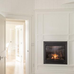 Foto de dormitorio principal, de estilo americano, con paredes blancas, suelo de madera clara, chimenea tradicional y marco de chimenea de madera