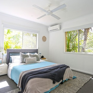 This is an example of a beach style guest bedroom in Other with white walls, carpet and grey floor.