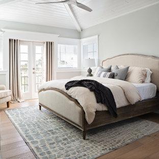 Großes Maritimes Hauptschlafzimmer mit grauer Wandfarbe, braunem Holzboden, beigem Boden und Holzwänden in Tampa