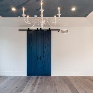 Diseño de dormitorio principal, marinero, grande, con paredes blancas, suelo de madera clara, chimenea tradicional y marco de chimenea de ladrillo