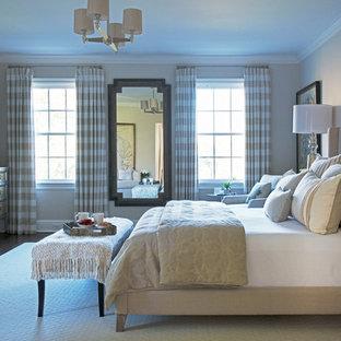 Modelo de dormitorio principal, clásico renovado, con paredes beige, suelo de madera oscura, chimenea tradicional y marco de chimenea de piedra