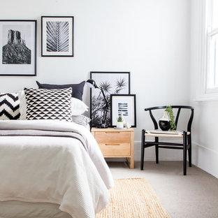 Inredning av ett skandinaviskt mellanstort sovrum, med vita väggar, heltäckningsmatta och beiget golv