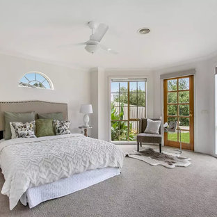 This is an example of a large transitional master bedroom in Melbourne with white walls, carpet and grey floor.