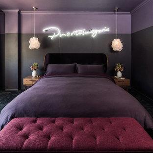 Foto di una camera matrimoniale design con moquette, pavimento nero e pareti viola