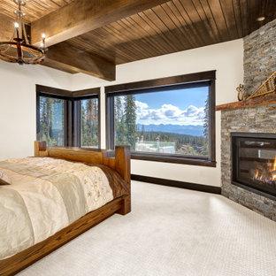 Exemple d'une chambre montagne avec un mur blanc, un sol en carrelage de céramique, une cheminée d'angle, un manteau de cheminée en pierre de parement, un sol gris, un plafond en poutres apparentes et un plafond en bois.