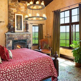 Idee per una camera matrimoniale american style con pareti arancioni, camino classico e cornice del camino in pietra