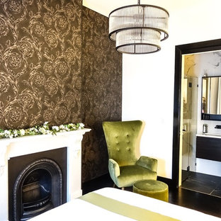 Example of a mid-sized transitional guest dark wood floor and black floor bedroom design in Sydney with white walls, a standard fireplace and a stone fireplace