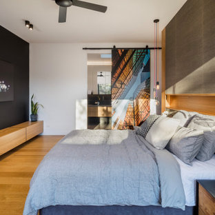Design ideas for a large contemporary master bedroom in Melbourne with grey walls, brown floor and medium hardwood floors.