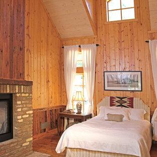 Diseño de dormitorio de estilo de casa de campo, de tamaño medio, con suelo de madera en tonos medios, chimenea de doble cara y marco de chimenea de ladrillo