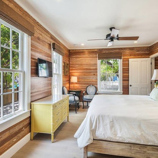 This is an example of a beach style guest bedroom in Miami with brown walls and grey floor.