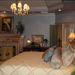 На фото: хозяйская спальня среднего размера в викторианском стиле с синими стенами, полом из травертина, стандартным камином и фасадом камина из камня