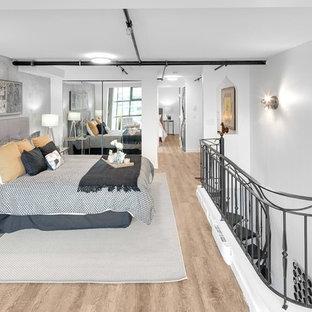 Idée de décoration pour une chambre mansardée ou avec mezzanine urbaine avec un mur gris, un sol en bois clair et aucune cheminée.