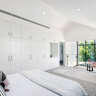 This is an example of a contemporary loft-style bedroom in Sydney with white walls, carpet, no fireplace and grey floor.